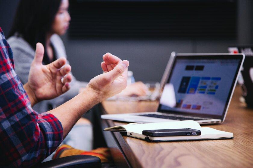 Eine Person gestikuliert mit ihren Händen vor einem Laptop.