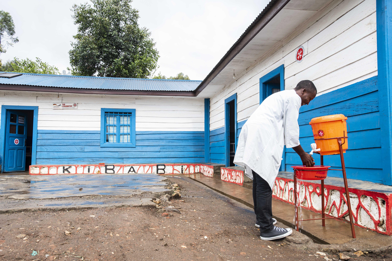 A man is washing his hands at a handwashing basin