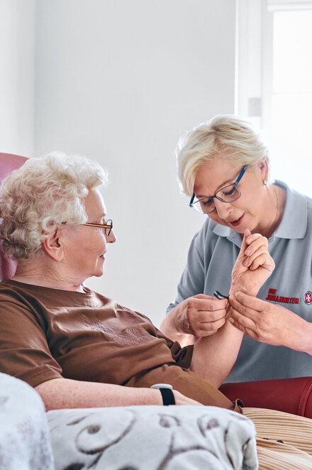 Eine Frau hilft einer älteren Dame