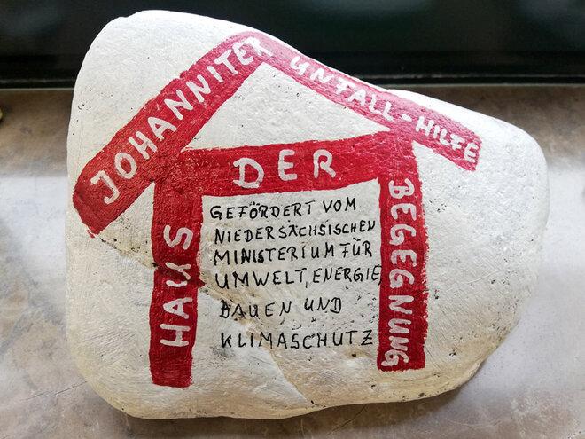"""Auf dem weißen Stein ist ein rotes Haus mit dem Text """"Haus der Begegnung"""" aufgemalt. Auf dem Dach des Hauses steht """"Johanniter-Unfall-Hilfe""""."""