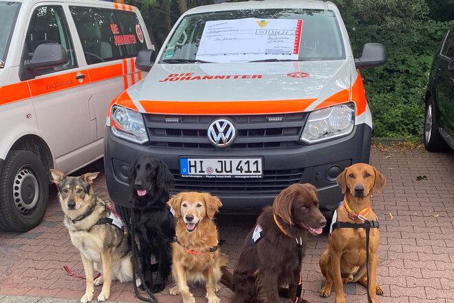 4 Hunde sitzen vor einem Einsatzfahrzeug auf dem ein symbolischer Scheck liegt