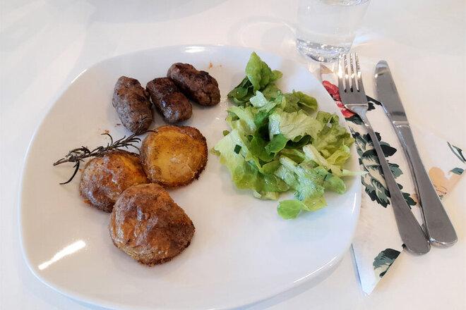 Fertiges Gericht mit Salat und Cevapcici, leckere auf einem Teller angerichtet.