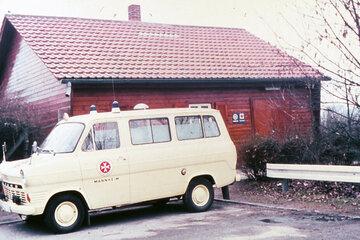 Ein Rettungswagen aus dem Jahr 1964 vor einem Holzhaus
