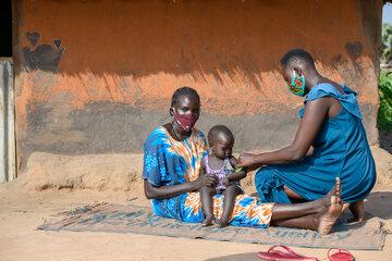 Amin untersucht ein Kind, das auf dem Arm seiner Mutter ist.