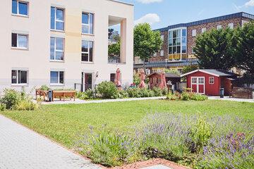 Blick auf die Fassade mit Sitzgelegenheiten und schönen Grünflächen davor