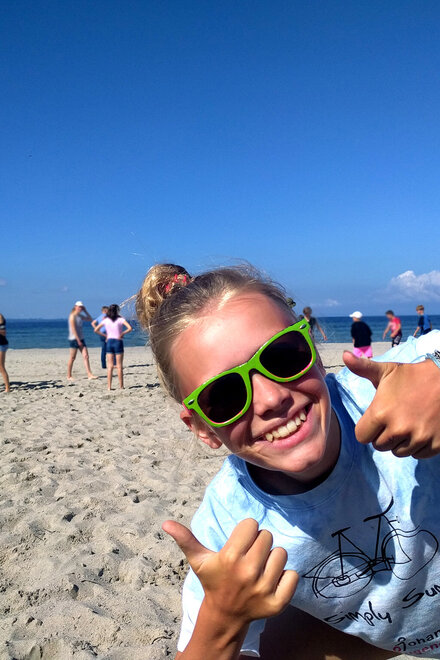Ein Mädchen mit Sonnenbrille am Strand guckt in die Kamera und zeigt beide Daumen hoch.