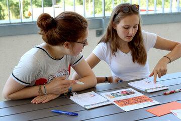 Zwei Mädchen diskutieren über Arbeitsblätter und Mitschriften, die vor ihnen liegen.