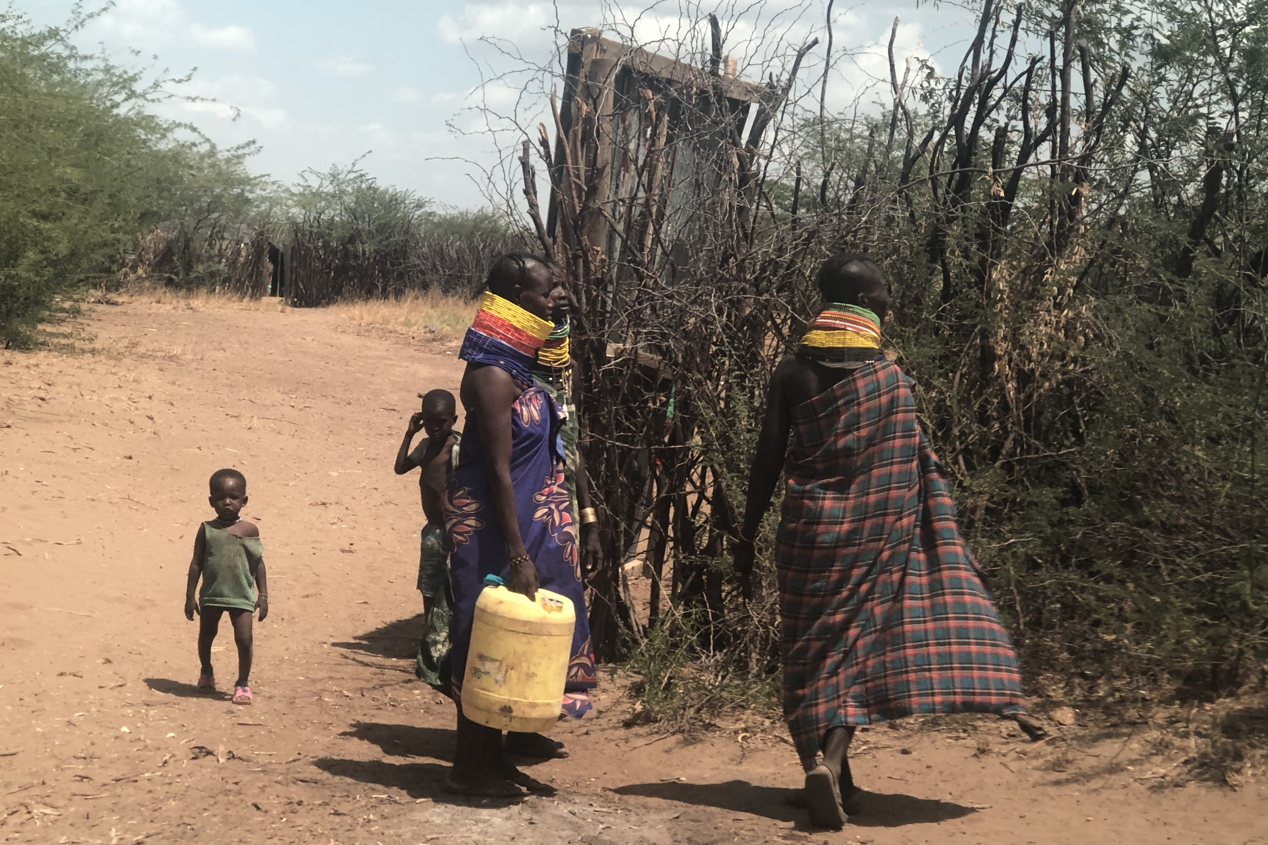 Two women with water canisters and two children on a dry road