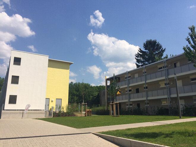 Außenansicht der Gebäube und des Innenhofes mit Grünflächen.
