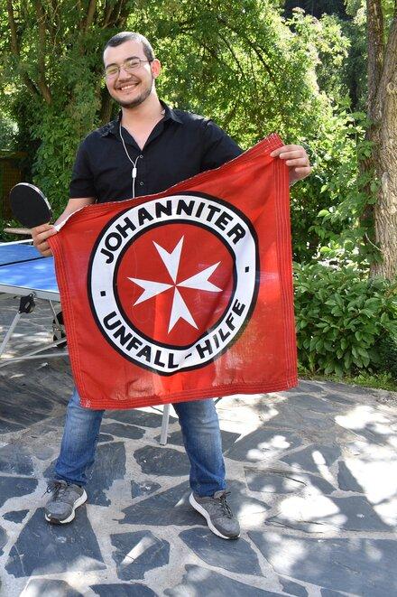 Junger flüchtling mit Johanniter Fahne im Garten der Waldracher Einrichtung.