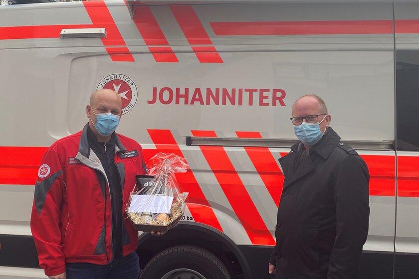 Zwei Männer vor einem Rettungswagen. Einer hat einen Präsentkorb