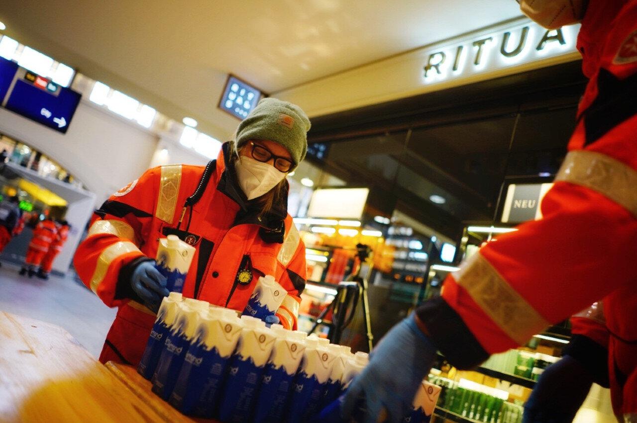 Ehrenamtliche der Johanniter-Kältehilfe verteilen Lebensmittel an Obdachlose.