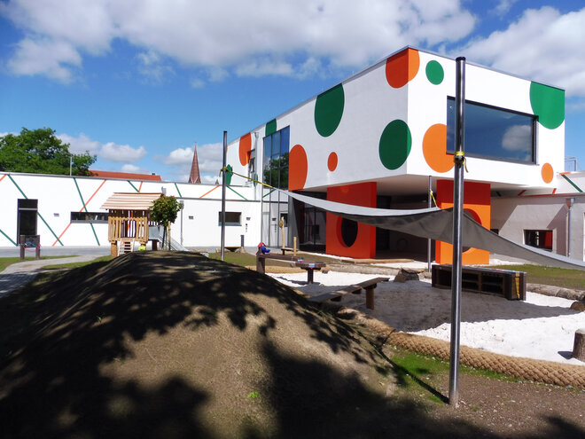 Ein Gebäude mit Spielgeräten für Kinder im Vordergrund