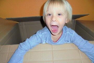 Ein Junge hockt im Papp-Karton und lacht.