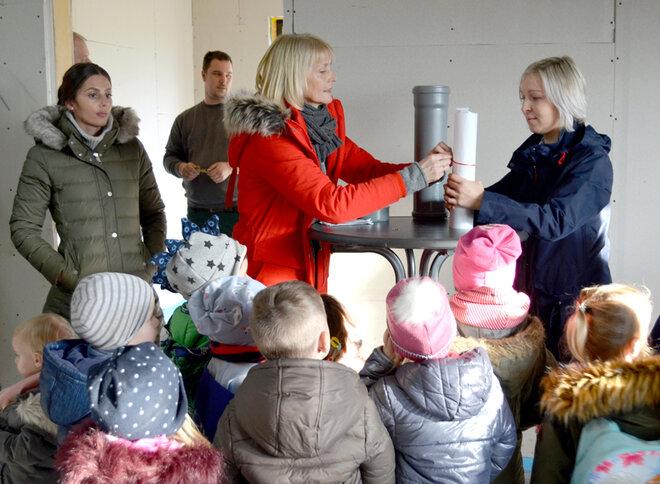 Einrichtungsleitung Nicola Lahl befüllt die Zeitkapsel und die Kita-Kinder schauen ihr dabei zu.