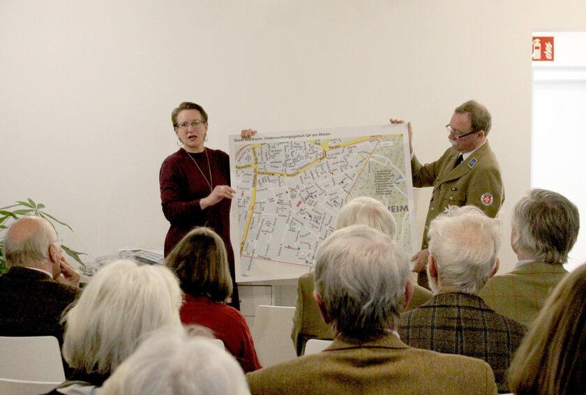 Ein Mann und eine Frau halten ein Bild mit einem Stadtplan vor Zuschauern hoch