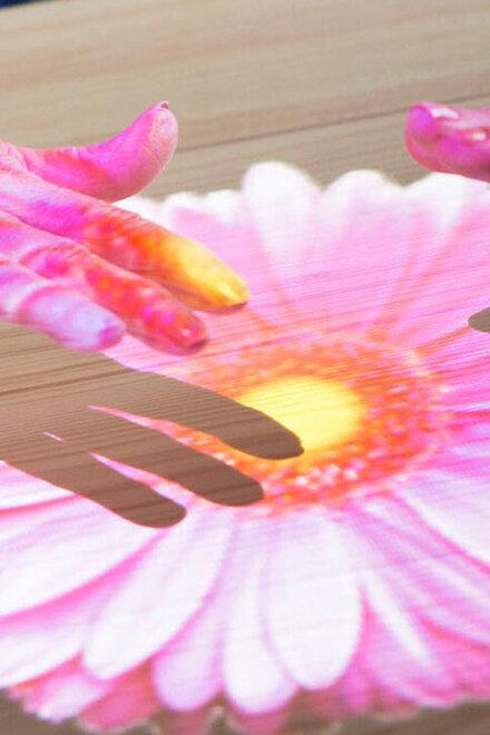 Hände auf einem  Blumenbild, das über die Tovertafel auf einen Tisch projiziert ist.