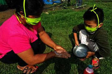 Eine Frau und ein Kind waschen sich die Hände. Beide tragen eine Maske