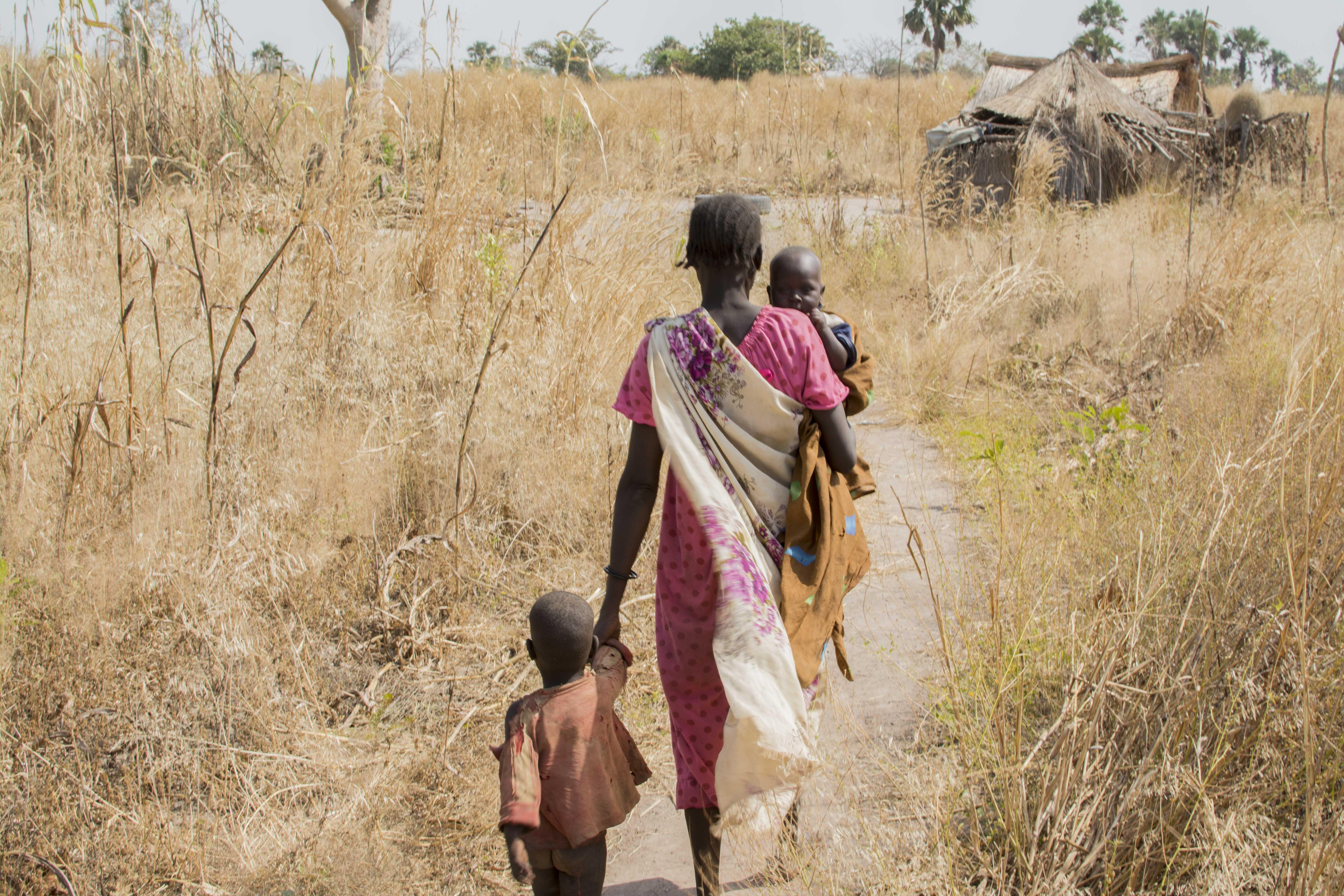 Eine Frau mit ihren zwei Kindern auf dem Weg nach Hause