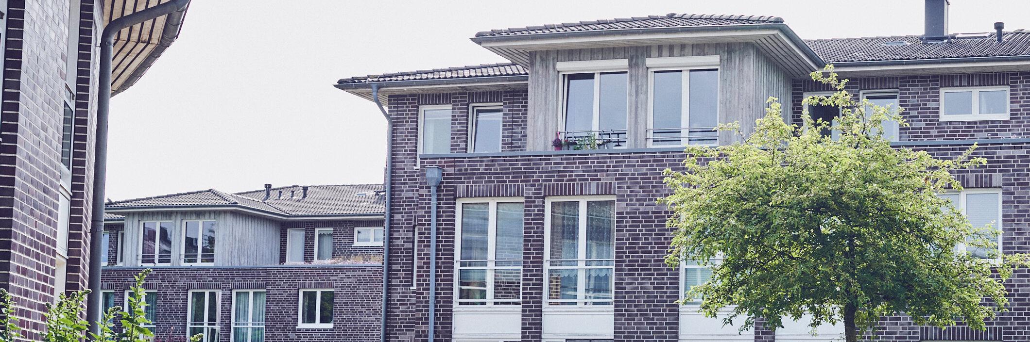 Von der Einfahrt kommend Blick auf mehrere gepflegte verklinkerte Häuser der Johanniter Seniorenanlage Heinrich-Gau in Wedel