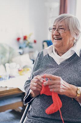 Eine Seniorin in grauem Pullover strickt