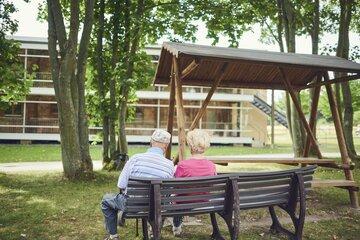 Zwei Bewohner sitzen im Park der Senioren-Wohnanlage
