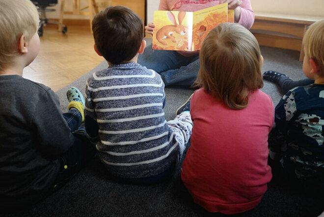 Kinder schauen sich gemeinsam mit der Erzieherin ein Bild zum Thema Herbst an.