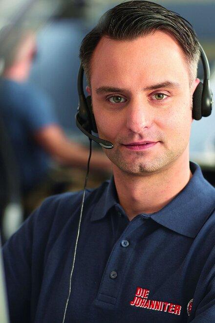 Johanniter-Mitarbeiter telefoniert in der Hausnotruf-Zentrale