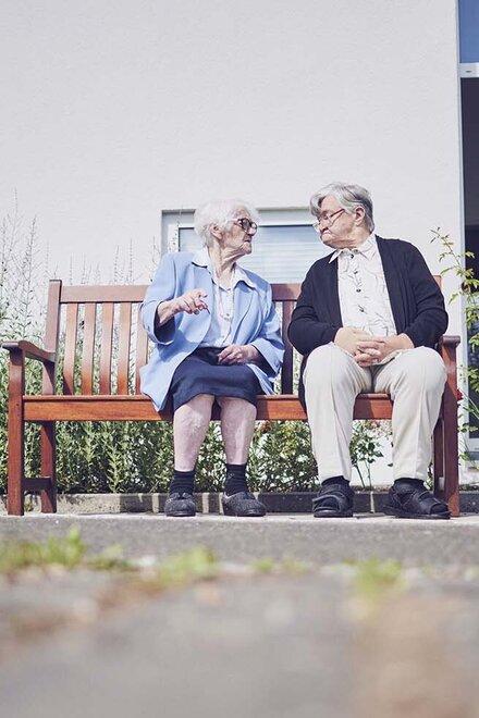Eine Bewohnerin und ei Bewohner sitzen auf einer Parkbank