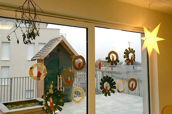 Selbstgebastelte kleine Adventskränze aus Tonkarton dekorieren die Fensterscheiben der Kita.
