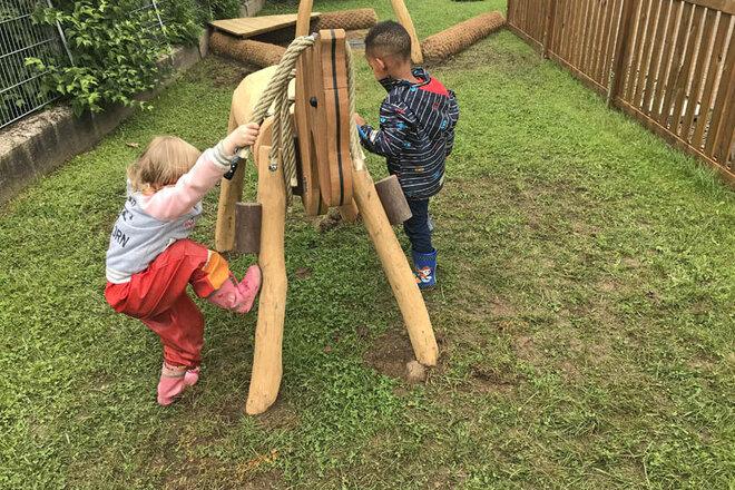 Zwei Kita-Kinder spielen im Außengelände mit dem neuen Holzpferd.