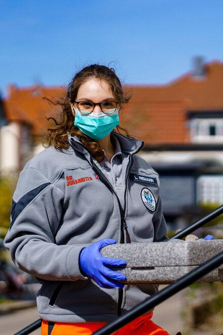 Eine Helferin der Johanniter-Unfall-Hilfe liefert kontaktos ein Mittagessen aus.