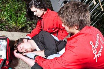 Zwei Schulsanitäter*innen versorgen einen Jungen mit Kopfverletzung.