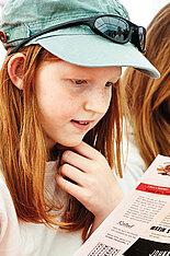 Zwei Mädchen sitzen nebeneinander, eine liest in einer Zeitschrift.