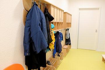 Große und kleine Jacken in allen Farben und kleine Schuhe sind zu sehen.