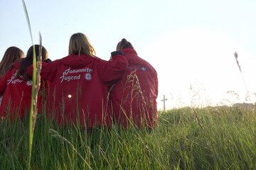 Vier Mädchen in Johanniter-Jugend-Kleidung sitzen auf einer Wiese und halten sich in den Armen. Im Hintergrund ist ein Kreuz zu sehen.