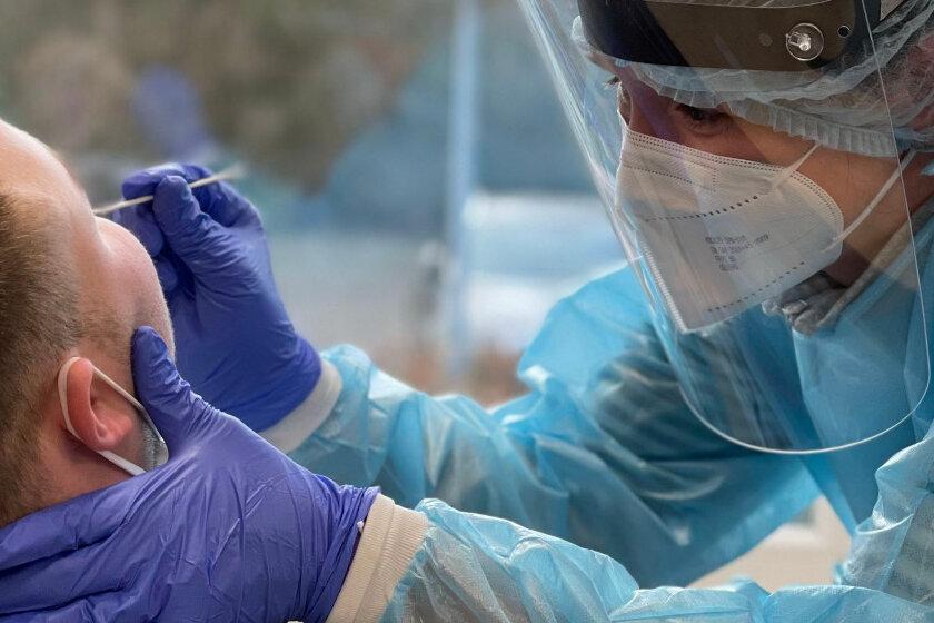 Eine Mitarbeiterin der Johanniter-Unfall-Hilfe macht einen Abstrich für einen Corona-Test bei einem Patienten.