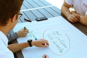 """Ein Jugendlicher schreibt auf ein Plakat mit der Überschrift """"Der/die perfekte SSD-Leiter*in"""""""