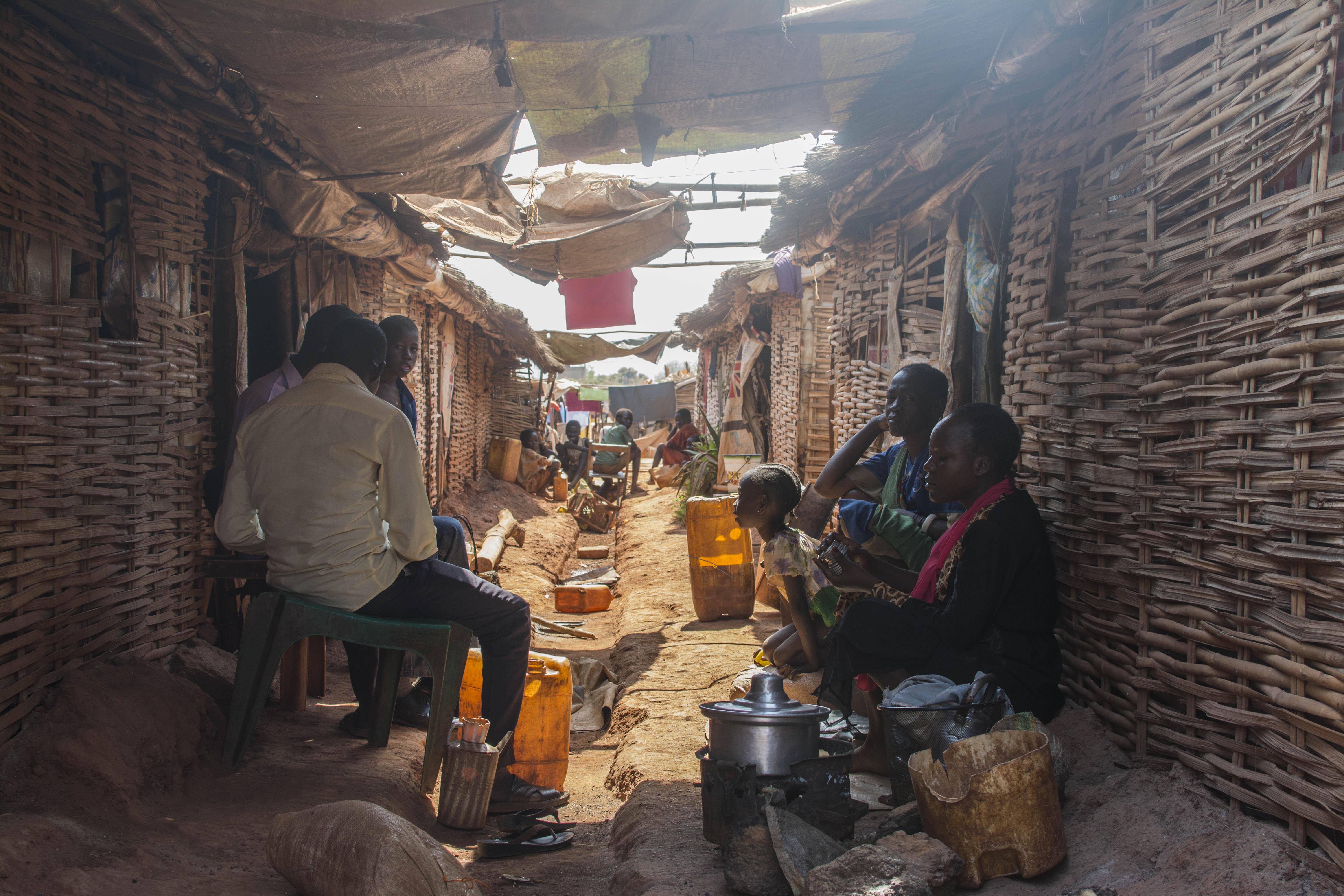 Menschen sitzen vor provisorischen Hütten