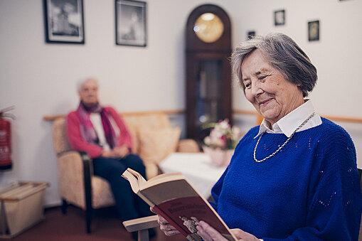 Eine Bewohnerin in blauem Pullover liest