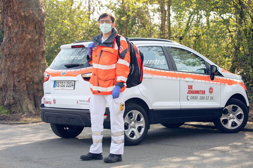 Johanniter-Mitarbeiter in Einsatzkleidung, Mundschutz und Handschuhen vor seinem Fahrzeug.