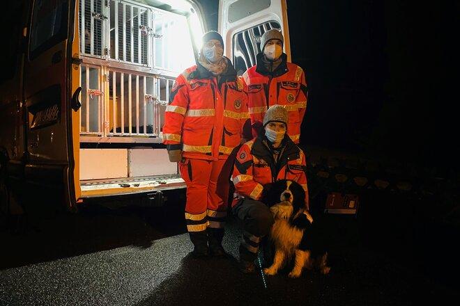 Drei Einsatzkräfte und ein Hund vor einem Einsatzwagen