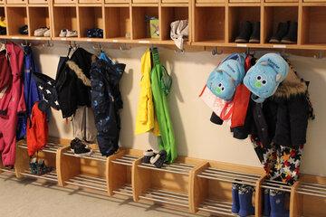 Kinderjacken, Rucksäcke und kleine Hausschuhe in allen Farben zieren die Garderobe der Kita am Wieter.