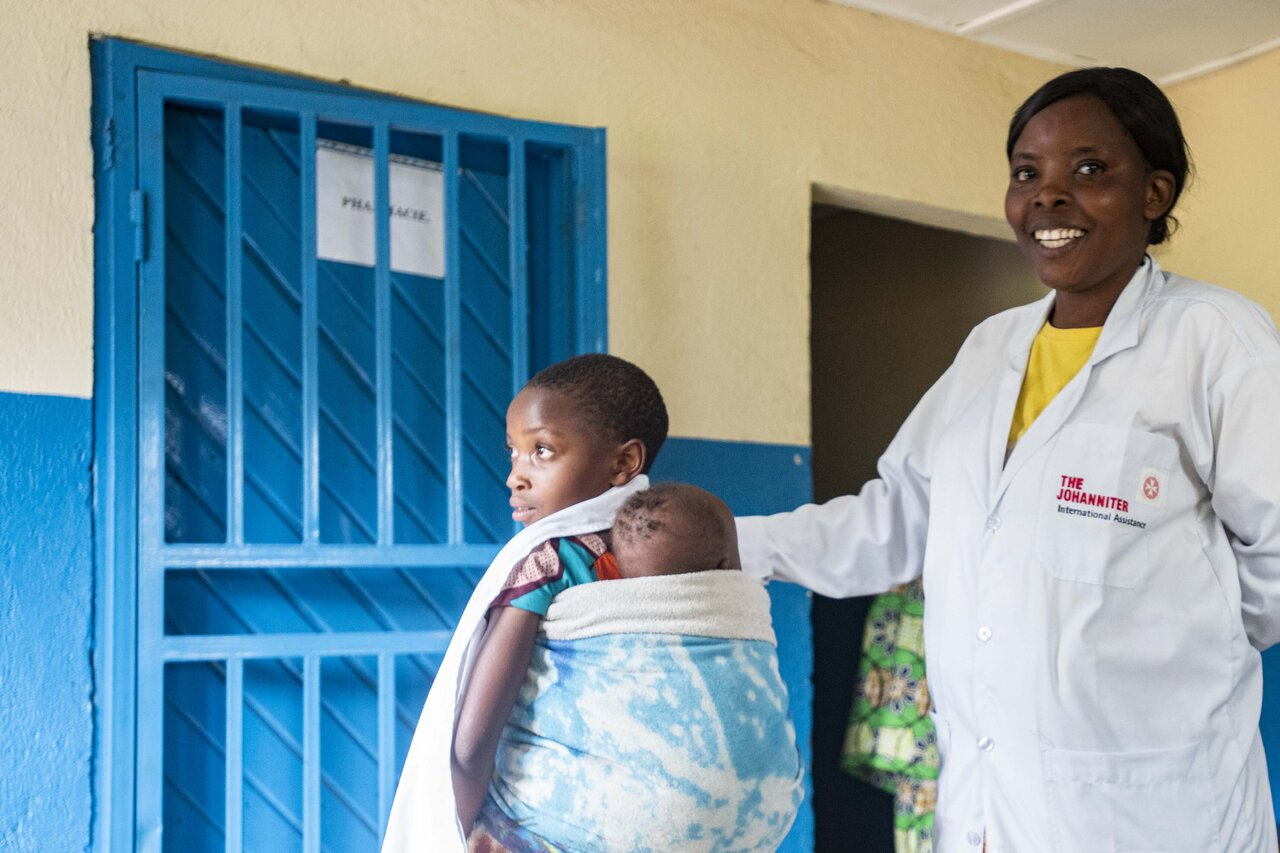 Nurse in health station in North Kivu touches a young child on her mother's back, smiling