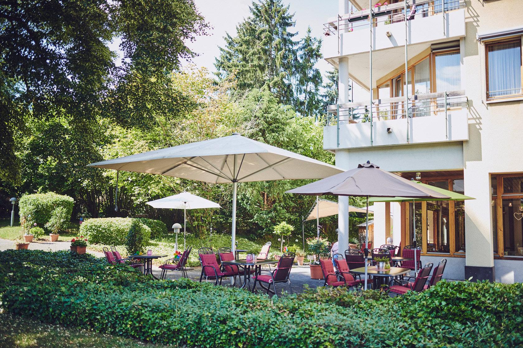 Sonnenschirme, Gartenmöbel mit roten Sitzauflagen im Außenbereich Johanniterhaus Sinzig