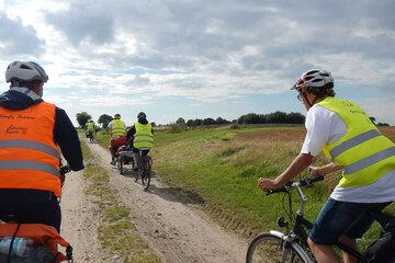 Jugendliche fahren mit Fahrrädern und Gepäcktaschen auf einem Feldweg