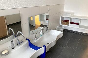 Sehr tiefhängende Waschbecken und kleine Spiegel.