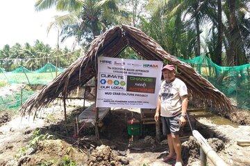 Ein Mann steht vor einer Holzhütte mit einem Banner des Projekts