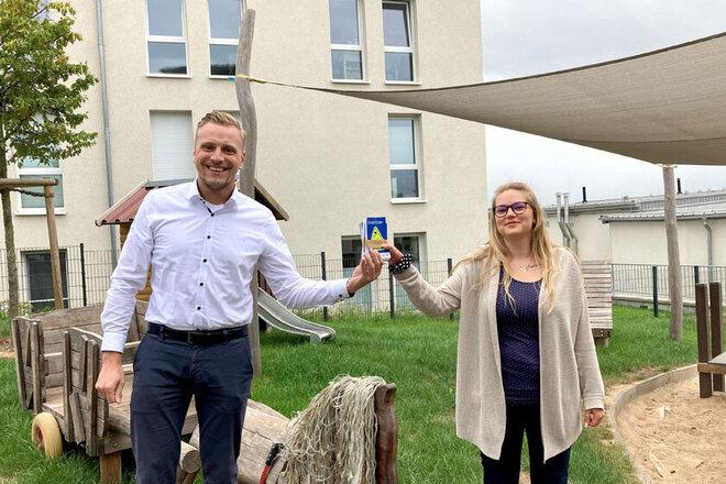 Dennis Schreiber (Vertreter der VGH in Northeim) übergibt die Kinderfinder an Tanja Schmidt (Einrichtungsleiterin der Kita am Wieter). Im Hintergrund sieht man die Außenspielgeräte der Kita.