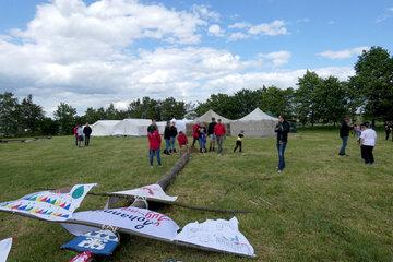 Ein Mast liegt auf einer Wiese. An diesem Mast sind verschiedene Banner befestigt. Im Hintergrund stehen Zelte.